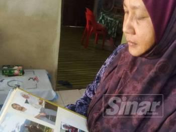 Maziatuzna melihat foto Allahyarham suaminya ketika ditemui di Kampung Kodiang Lama Luar, Mukim Keplu semalam.