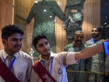 Beberapa pelajar berswafoto di hadapan patung Varthaman (dua, kanan) yang pesawatnya ditembak jatuh di ruang udara Kashmir pada awal tahun lalu. - Foto AFP