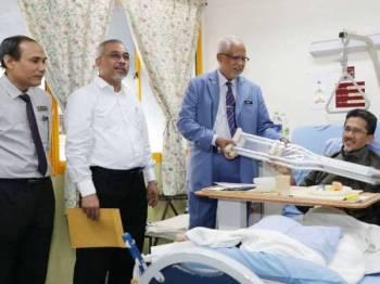 Mahfuz Omar menyampaikan sumbangan tongkat kepada Ahmad Taufiq.
