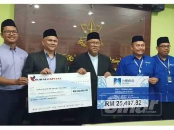 Halidan (tengah) bersama pembayar zakat perniagaan pada majlis serahan zakat perniagaan badan korporat Rural Capital Berhad dan MBSB Bank Berhad yang dianggarkan bernilai RM94.447.82 di Ibu Pejabat PKZ hari ini.