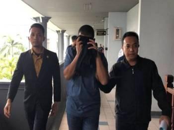 Mohd Hanafi (tengah) ketika hadir ke mahkamah di sini hari ini.