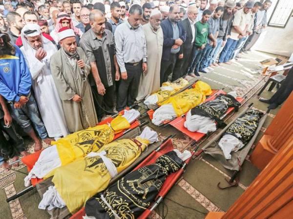 Penduduk Palestin menunaikan solat jenazah lapan sekeluarga yang terbunuh dalam serangan udara dilancarkan Israel di Deir al-Balah di selatan Gaza.