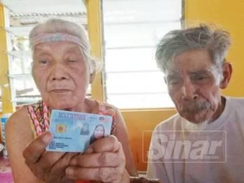Jenab (kiri) menunjukkan MyKad sambil ditemani Salleh di rumahnya di Kampung Rambah, Pontian.