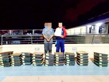 Dua lelaki bersama sangkar burung yang dirampas dalam penahanan berkenaan.