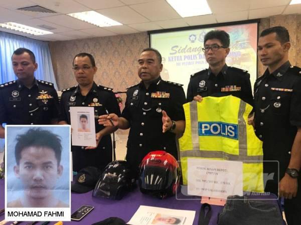 Osman (tengah) menunjukkan barang-barang yang dirampas daripada dua suspek yang menyamar sebagai anggota polis sebelum melakukan jenayah samun.
