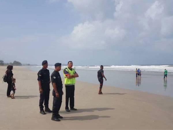 Mohd Zain (kanan) bersama dua anggotanya turun padang meninjau aktiviti pengunjung mengutip kerang bulu di Pulau Kekabu, di sini.