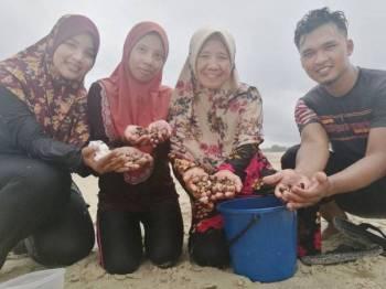 Roriah (dua dari kanan) bersama Norul Asmahanim (dua dari kiri) dan Noelawati mencari kerang di pantai Rhu Dua di sini.