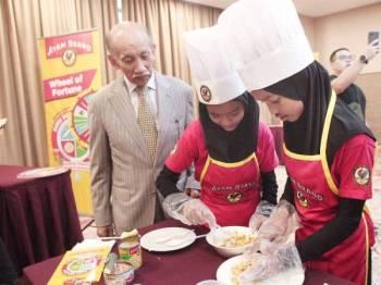 Mu'tamir (kiri) melihat aktiviti yang dilakukan peserta Pertandingan Ayam Brand Suku-Suku Separuh di Hospital KPJ Ampang, Kuala Lumpur kelmarin.