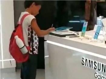 Guilherme Santiago menyiapkan kerja sekolah di sebuah kedai elektronik.