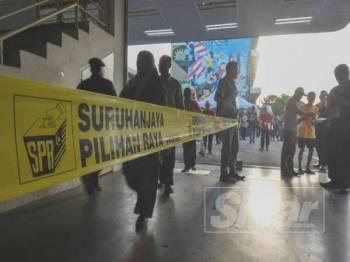 Proses mengundi berjalan lancar dengan bantuan petugas daripada Suruhanjaya Pilihan Raya (SPR). - Foto SHARIFUDIN ABDUL RAHIM
