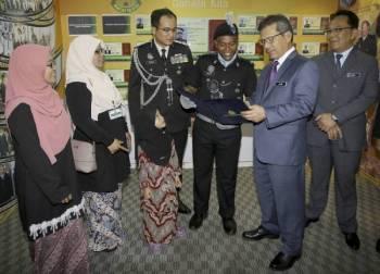 Alwi (dua dari kanan) beramah mesra dengan Penerima Kadet Terbaik Anugerah Ketua Pengarah Imigresen, Amirul Fauzan Hassan Zaim (empat dari kiri) pada Majlis Perbarisan Tamat Latihan Kursus Asas Pegawai Imigresen Gred KP 19 Siri 3 2019 di Akademi Imigresen Malaysia hari ini. -Foto Bernama