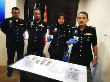 Adzli (kanan) menunjukkan dadah yang dirampas ketika serbuan dilakukan di Gurun pagi kelmarin.