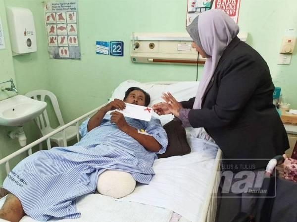 Rafidah menyampaikan pampasan hilang upaya sementara kepada Mukhtar.