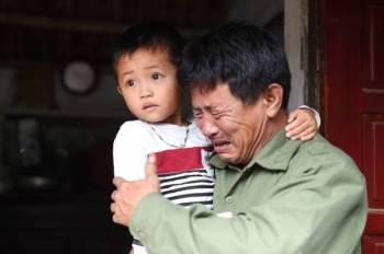 Le Minh Tuan, ayah kepada Le Van Ha antara migran Vietnam yang ditemui maut dalam kontena sejuk beku di Britain menangis sambil memeluk cucunya. - Foto AFP