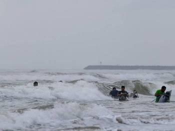 Sekumpulan lelaki mencari kerang dalam keadaan ombak bergelora ketika tinjauan di Pantai Rhu Dua hari ini. - Foto Bernama