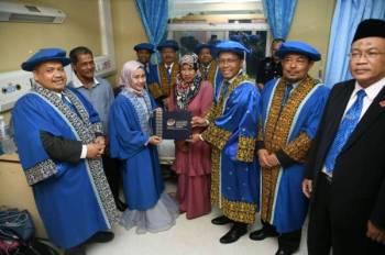 Dr R Badlishah Ahmad menyampaikan skrol Ijazah Sarjana Muda Komunikasi Media Baharu kepada Nur Izyan disaksikan pengurusan tertinggi universiti. Turut kelihatan Dr Huzili dan Dr Abdul Karim.
