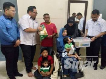 Mohd Aqmal (kanan) menyerahkan sumbangan barangan keperluan harian kepada seorang penerima zakat LZS pada Program Ziarah Agensi Lembaga Zakat Selangor bersama Tenaga Nasional Berhad (TNB) Cawangan Cheras di daerah Hulu Langat di sini hari ini.
