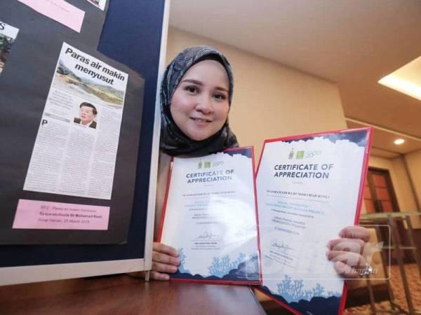 Syajaratulhuda memegang sijil kedua-dua anugerah yang dimenanginya di samping salah satu artikel.