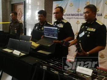 Khairul Dzaimee (dua dari kanan) menunjukkan barang rampasan hasil serbuan itu pada sidang media di JIM Putrajaya di sini hari ini.