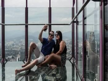 Mohammed Ehtsham (kiri) dan Maham Ehtsham dari England bergambar berlatarbelakangkan panorama bandar dari dalam Sky Box di Menara KL. - AFP