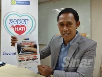 Mohd Sabirin menunjukkan risalah berkenaan E-Majikan yang disediakan LZS.