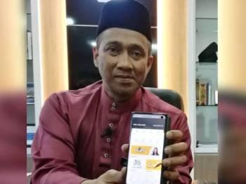 Mohammad Fakhruddin menunjukkan aplikasi Pahang Go yang dilancarkan dan mula digunakan orang ramai.