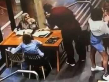 Rakaman kamera keselamatan menunjukkan seorang lelaki menghampiri sebuah meja diduduki tiga wanita bertudung yang sedang berbual di sebuah kafe di Sydney pada Rabu lalu.
