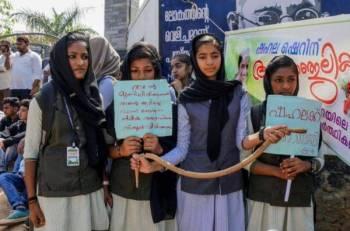 Pelajar sebuah sekolah di Kerala, India memegang plakad dan ular mainan ketika protes berhubung kematian pelajar berusia 10 tahun akibat dipatuk ular di dalam kelas. - Foto AFP