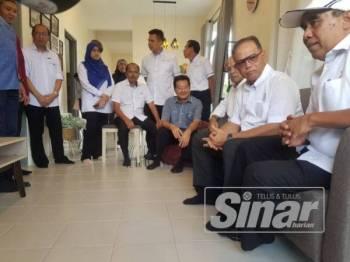 Abd Rahim (kanan) dan Wan Rosdy (dua dari kanan) berehat di ruang tamu rumah Makmur di Kampung Tiram hari ini.