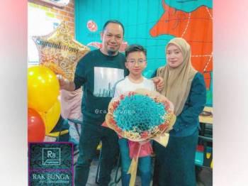 Nor Ashikin (kanan) dan suaminya, Ihsan merakamkan gambar bersama Muhammad Danish yang memegang jambangan bunga yang digubah menggunakan wang tunai bernilai RM10,000.