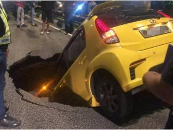 Keadaan Perodua Myvi yang terperosok ke dalam lubang akibat tanah mendap di Jalan Maharajalela malam tadi.