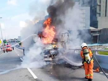 Anggota bomba memadamkan kebakaran melibatkan sebuah lori berhampiran Jambatan Motorola di sini pagi tadi