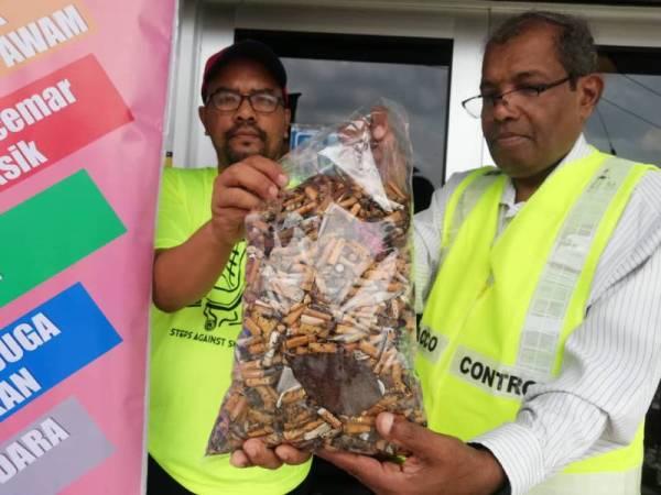 Muhammad Sha'ani (kanan) dan Azkandar menunjukkan ribuan puntung rokok yang berjaya dikutip sempena kempen tersebut di beberapa lokasi hari ini.