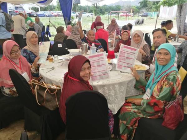 Fatimah (depan) bersama sebahagian penerima surat hak milik tanah yang diserahkan menteri besar sempena Majlis Ramah Mesra dan Penyerahan Surat Hak Milik Kampung Seri Mahkota di sini hari ini.