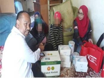 Muhammad Faidulatraf (kiri) menyerahkan Kit Bantuan Makanan Asasi LZNK dan wang ihsan kecemasan kepada Rushitta (dua dari kiri) sambil diperhatikan Zuraini (kanan) di Kampung Berjaya di sini.