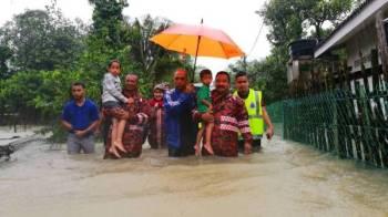 Anggota penyelamat dan Wan Hassan (dua dari kanan) menyelamatkan mangsa banjir di Kampung Gong Cokoh.