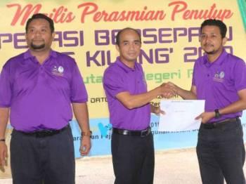 Grippin (tengah) menyampaikan sijil penyertaan kepada Penolong Pengarah Kanan Penguatkuasa Zon Pahang Timur Muhammad Firdaus Abdul Karim pada majlis penutup operasi bersepadu Op Kilang di pekarangan Pejabat Pembangunan Hutan Bukit Sekilau hari ini.