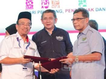 Salahuddin (tengah) menyaksikan pertukaran memorandum persefahaman di antara Pengerusi Ahli Jemaah Pengarah Pertubuhan Peladang Kebangsaan (NAFAS), Datuk Phahrolrazi Mohd Zawawi (kiri) dan Pengerusi Ahli Jemaah Pengarah Pertubuhan Peladang Negeri Johor (PPNJ), Omar Salleh pada Majlis Penutupan HPPNK 2019 semalam. -FOTO ZAHID IZZANI