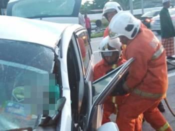 Anggota bomba menjalankan operasi bagi mengeluarkan mangsa yang tersepit dalam kenderaan. Foto: Pembaca