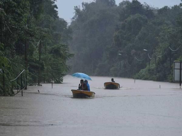 Mangsa banjir menggunakan sampan untuk berulang alik dari Kampung Bukit Payung ke Kampung Keruak, Besut, Terengganu, selepas jalan yang menghubungkan kedua-dua kampung terputus ekoran banjir semalam.  - Foto Bernama