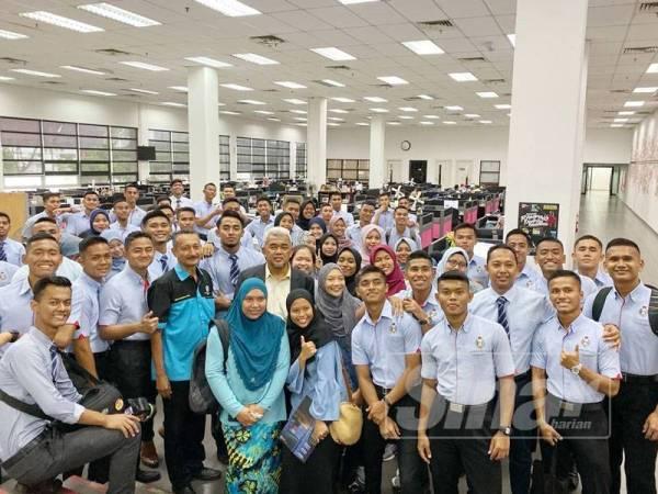 Abdul Rahman (lima dari kiri) dan warga UPNM bergambar di ruangan Sinar Harian.