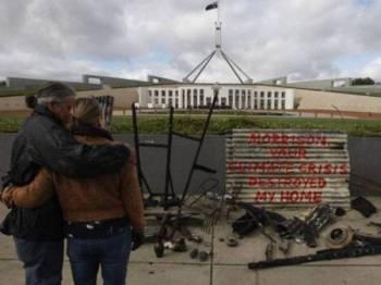 Plesman bersama pasangannya membawa sisa serpihan rumah mereka yang musnah terbakar di luar bangunan Parlimen di Canberra kelmarin. - Foto Agensi