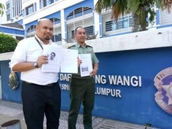 Izmil (kiri) menunjukkan laporan polis di hadapan Ibu Pejabat Polis Daerah Dang Wangi.