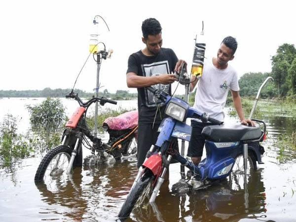 Muhammad Zakaria Mat Kail, 22, (kiri) dan abangnya Ikram Shahidi, 24, memeriksa karburetor yang telah diubahsuai bagi membolehkan motosikal meredah banjir dengan lancar ketika ditemui di Kampung Banggol.- Foto Bernama