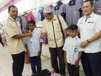 Andansura (kiri) menyarungkan pakaian sekolah kepada salah seorang penerima pada program kembali ke sekolah dan penyampaian baucar pembelian barangan kelengkapan persekolahan 2020 DUN Beserah di Pasaraya Sakan semalam.