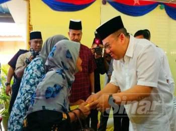 Dr Tengku Muhammad Fa-iz Petra (kanan) berkenan menyerahkan sumbangan kepada mangsa banjir di PPS SK Bakong.