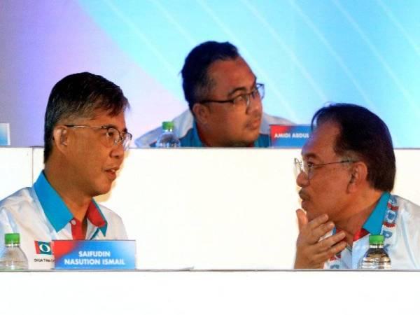 Anwar (kanan) menyatakan sesuatu kepada Tian Chua pada Kongres Nasional PKR di Pusat Dagangan Antarabangsa Melaka (MITC) Ayer Keroh hari ini. - Foto Bernama