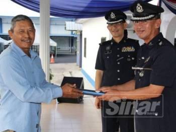 Nor Azmi (kanan) menyampaikan surat penghargaan kepada salah seorang penerima pada Perhimpunan Pagi IPD Sabak Bernam hari ini.