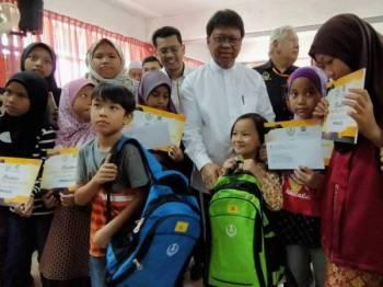 Asmuni (tengah) bersama pelajar-pelajar yang menerima set kelengkapan sekolah pada Majlis Penyerahan Sumbangan Back To School kepada 224 pelajar dan 20 Biasiswa Menteri Besar Perak di Sekolah Menengah Kebangsaan Dato Ahmad Said, Manjoi hari ini.