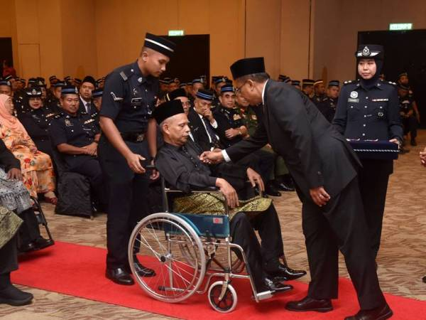 Abd Rahim (dua dari kanan) bersama Ketua Polis Negeri, Datuk Aidi Ismail (kanan) melihat pemakaian Pingat Jasa Pahlawan yang disempurnakan Ahmad Samsuri. -FOTO: Urusetia Penerangan Darul Iman (UPDI).